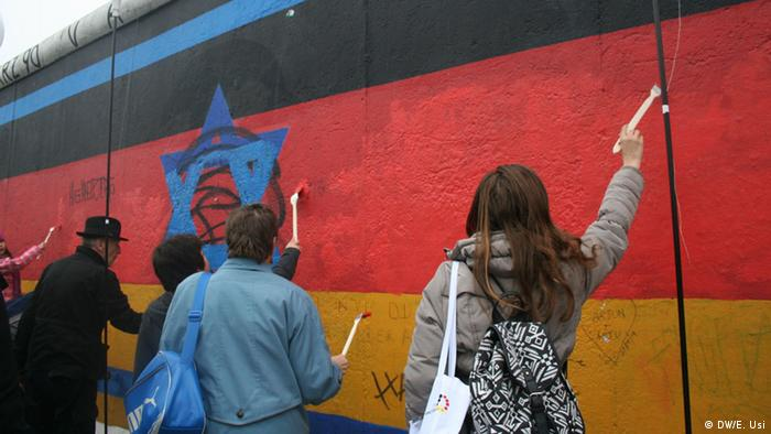 Volunteers enthusiastically help restore a mural in Berlin's East Side Gallery