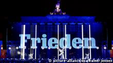 Germany's Brandenburg Gate illuminated with the German word for peace