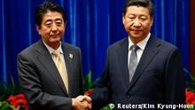 China's President Xi Jinping (R) shakes hands with Japan's Prime Minister Shinzo Abe during their meeting at the Great Hall of the People, on the sidelines of the Asia Pacific Economic Cooperation (APEC) meetings, in Beijing November 10, 2014. Xi and Abe held formal talks on Monday for the first time since the two leaders took office, a breakthrough in ending a two-year row between Asia's biggest economies over history and territory. REUTERS/Kim Kyung-Hoon (CHINA - Tags: POLITICS BUSINESS)