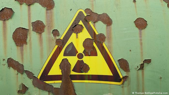 A radioaction symbol hangs on a wall