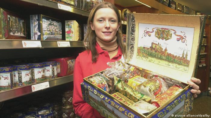 A woman holding up a festively decorated box containing Lebkuchen, German spiced gingerbread