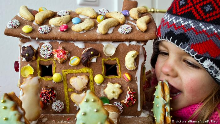 A child holding up a festively decorated gingebread house