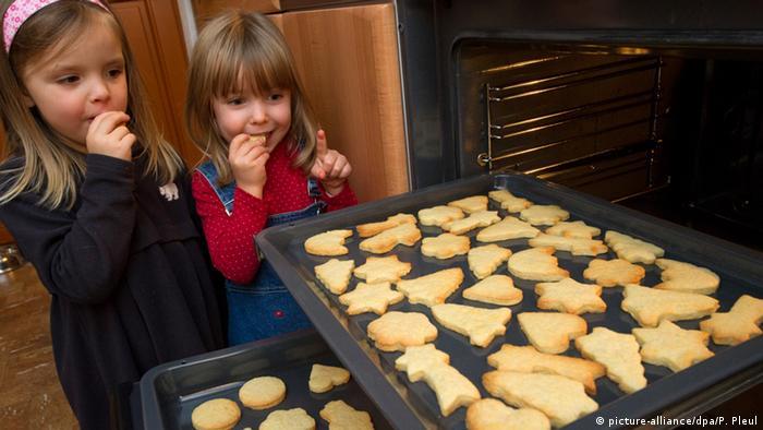 Zwei Mädchen stehen am offenen Ofen, auf dem Blech sind Ausstechplätzchen