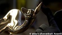 ***Bild des Tages mit Deutschlandbezug*** Ein Mann schleift am 06.11.2014 in Süssen (Baden-Württemberg) an einer Bronzefigur des Medien- und Fernsehpreises Bambi in der Gießerei Strassacker. Seit 1958 wird in der Gießerei Strassacker der Filmpreis Bambi gegossen. Foto: Daniel Naupold/dpa (zu dpa-KORR Aus der Gießerei in die Vitrine der Stars - die Geburt eines Bambis vom 10.11.2014)
