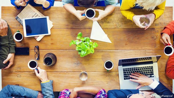 Mesa com computadores e xícaras de café