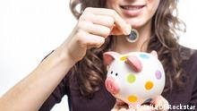 A woman puts a Euro coin into a piggy bank (Fotolia/DDRockstar)