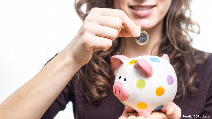 Junge Frau wirft Euromünze in Sparschwein