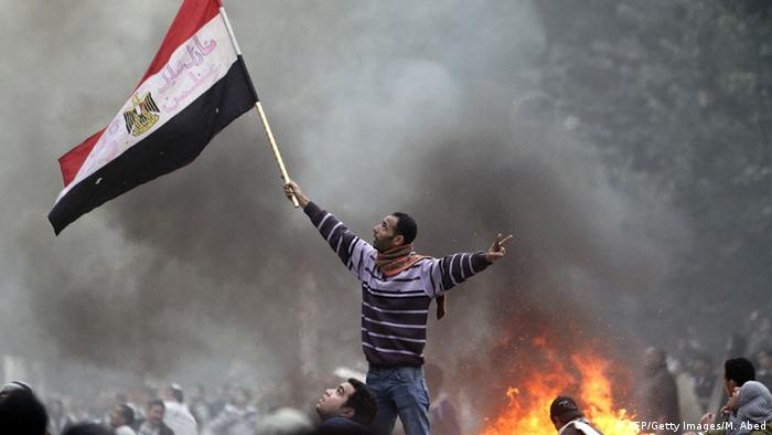 An Egyptian protester waves his national flag while making the victory sign outside the parliament building during clashes with soldiers near Cairo's Tahrir Square on December 16, 2011 (AFP/Getty Images/M. Abed)