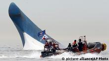 FILE - In this April 16, 2014 file photo, South Korean coast guard officers try to rescue passengers from the Sewol ferry as it sinks in the water off the southern coast near Jindo, south of Seoul, South Korea. The sinking, one of South Korea's deadliest disasters in decades, caused nationwide grief and fury, with authorities blaming overloading of cargo, improper storage, untimely rescue efforts and other negligence for the incident. After more than six months after the sinking, the bodies of 294 people have been retrieved but 10 others are still listed missing. (AP Photo/Yonhap, File) KOREA OUT