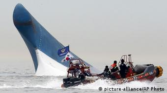 South Korean coast guard officers try to rescue passengers from the Sewol ferry as it sinks in the water off the southern coast near Jindo, south of Seoul, South Korea (AP Photo/Yonhap, File)
