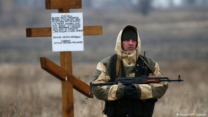 An armed separatist stands near the monument to those killed