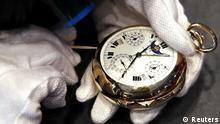 Zwei Hände in weißen Handschuhen reparieren eine teure Taschenuhr