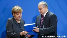 Christoph Schimdt, President of the Institute for Economic Research hands over the German Council of Economic Expert's (SVR) (Sachverstaendigenrat) 2014/2015 report to German Chancellor Angela Merkel at the Chancellery in Berlin November 12, 2014. Germany's panel of economic advisors, also known as 'the five wise men' released its annual report on economic development on Wednesday. REUTERS/Hannibal Hanschke (GERMANY - Tags: POLITICS)