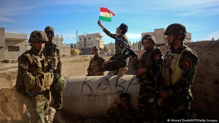 Peschmerga-Kämpfer schwenken in der umkämpften Stadt Kobane die kurdische Fahne, Foto: AFP