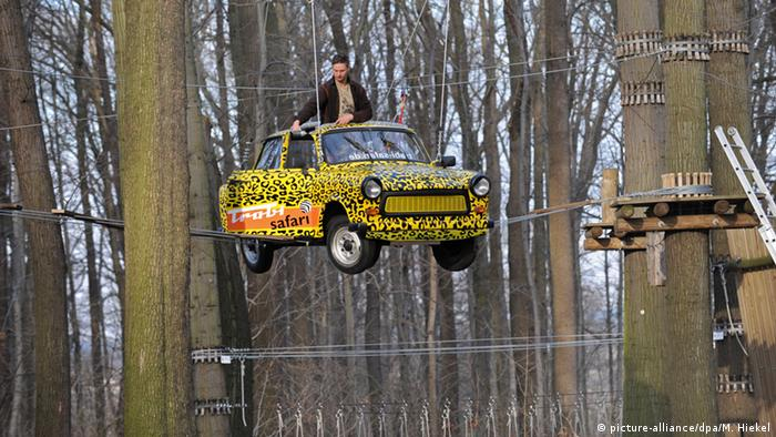 A yellow Trabant East German car is suspended in a forest climbing park, where the car becomes part of the climbing course.