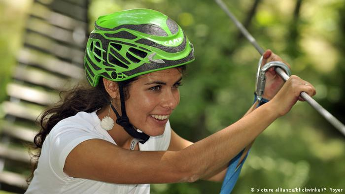 Woman wearing a green helmet with a rope and carbine attached to a safety cord is about to cross a pendant Bridge.