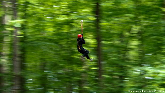 In a forest someone in a climbing harness is on a rope slide
