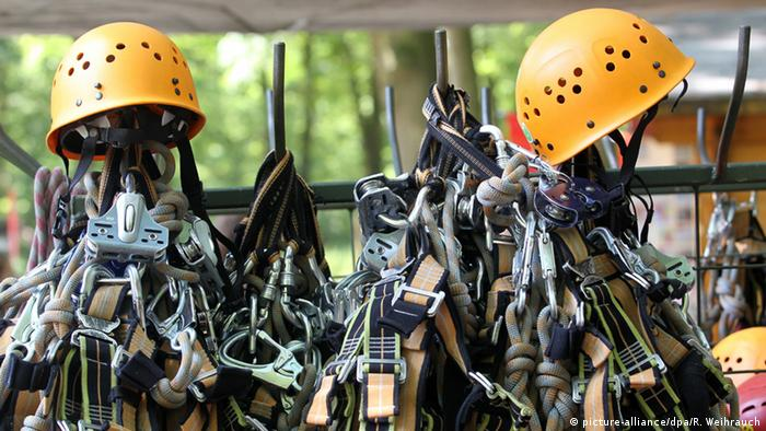 Hooks with yellow climbing helmets and climbing harnesses