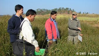Laotische Mitarbeiterin einer ausländischen Nichtregierungsorganisation beim Besuch eines Projekts in der Provinz Xieng Khouang, daneben Regierungsvertreter (Foto: DW/Esther Felden)