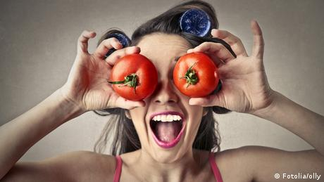 Frau hält sich Tomaten vor ihre Augen