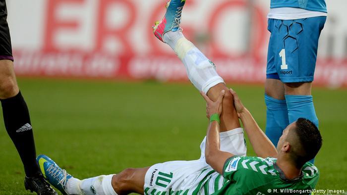 Ein Fußballspieler liegt auf dem Boden und hält mit den Händen sein Knie