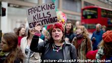 An environmental campaigner holds up a placard as she takes part in a protest with the theme of a Fracked Future Carnival against the practice of fracking being used in Britain, to coincide with a Shale Gas Forum being held today in London, Wednesday, March 19, 2014. Oil and gas developers employ hydraulic fracturing or fracking to boost production. The technique pumps water, fine sand and chemicals into wells to fracture open oil and gas-bearing rock deposits. The process has been controversial amid concern that fracking gone wrong could taint groundwater with hydrocarbons or fracking fluids containing toxic substances. (AP Photo/Matt Dunham)