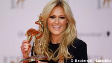 German singer Helene Fischer poses with her Entertainment trophy during the Bambi 2014 media awards ceremony in Berlin November 13, 2014. The annual Bambi awards honours celebrities from the world of entertainment, literature, sports and politics. REUTERS/Hannibal Hanschke (GERMANY - Tags: ENTERTAINMENT)