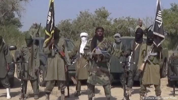 In an image taken from a Boko Haram video, the leader of the group Boko Haram is flanked by masked gunmen holding flags. Photo: (AP Photo)