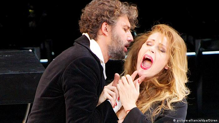 Jonas Kaufmann ad Kristine Opolais hold hands tightly and sing into each other's ears