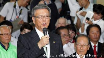 Takeshi Onaga speaks to a crowded room of supproters on election night, 2014, after winning the Okinawan race for governor.