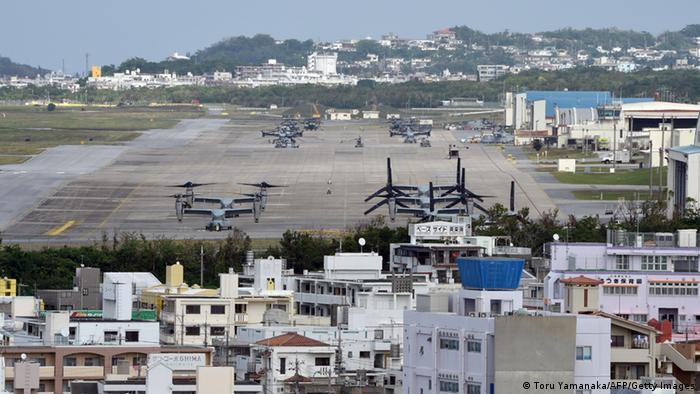 US Marine's Camp Futenma, on the Japanese Island of Okinawa, shows multi-mission tiltrotor Osprey aircraft in a crowded urban area.