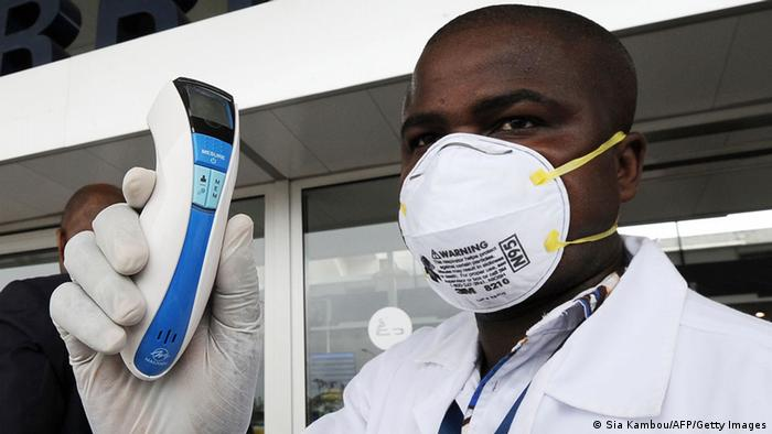 An agent of the national public health institute poses with a thermometer at the airport, in Abidjan on August 12, 2014, as part of protective measures against the Ebola virus.