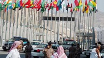 Saudis walk under flags of Muslim countries participating in the summit of the Organization of the Islamic Conference
