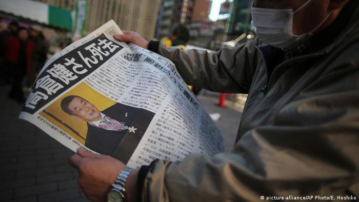 A pedestrian reads an extra edition of a newspaper with front page featuring an obituary notice of acclaimed Japanese film star Ken Takakura at Shimbashi Station in Tokyo, Tuesday, Nov. 18, 2014 (AP Photo/Eugene Hoshiko)