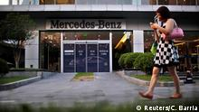 A woman walks past a Mercedes-Benz car dealership in downtown Shanghai in this August 5, 2014 file photo. Daimler AG will give its new luxury baby, the Mercedes-Maybach limousine, a glitzy world debut at this week's Guangzhou autoshow in China, even as analysts warn the end is nigh for the country's 10-year high-end car sales boom. REUTERS/Carlos Barria/Files (CHINA - Tags: TRANSPORT BUSINESS)