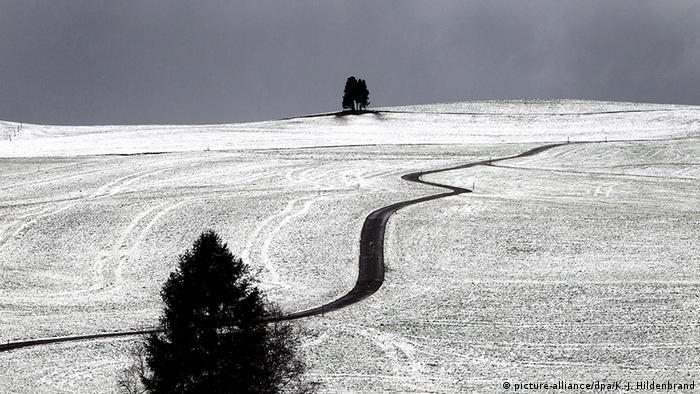 Ein Weg schlängelt sich am durch schneebedeckte Felder