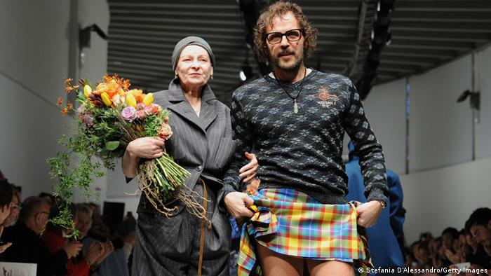Vivienne Westwood mit Blumen im Arm und eingehakt bei Andreas Kronthaler auf dem Catwalk