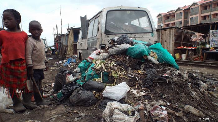 Two children stand beside a pile of sewage at Nairobi's Kibera slum