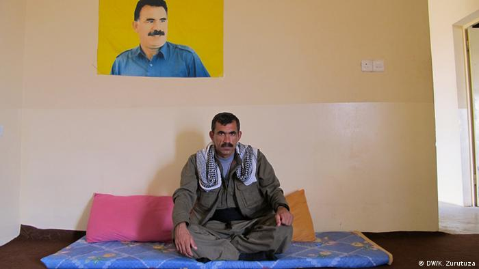 Agid sits on the floor beneath a poster of PKK leader Ocalan in the unit's headquarters