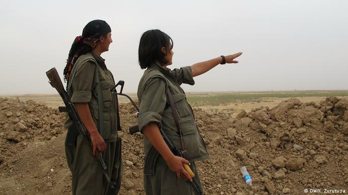 Two female PKK fighters stand at the front