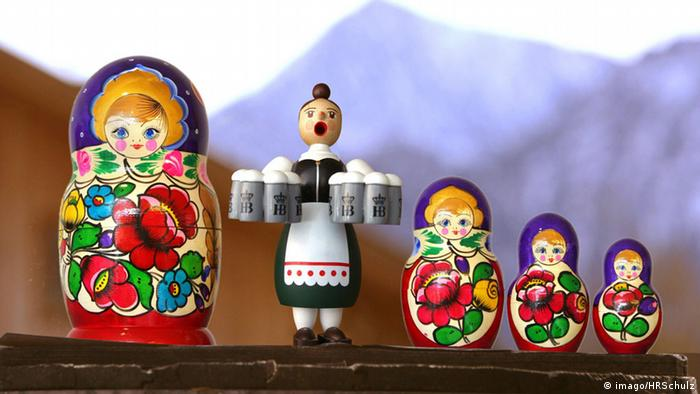 A matryoshka doll alongside a German doll holding beer steins (imago/HRSchulz)