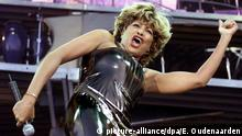 Tina Turner singing on stage in a black leather outfit