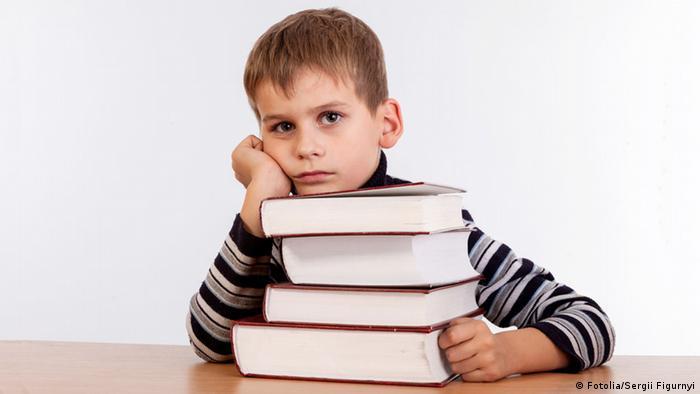 Zabrinut izraz lica dječaka ispred kojeg su na stolu četiri debele knjige (Symbolbild)