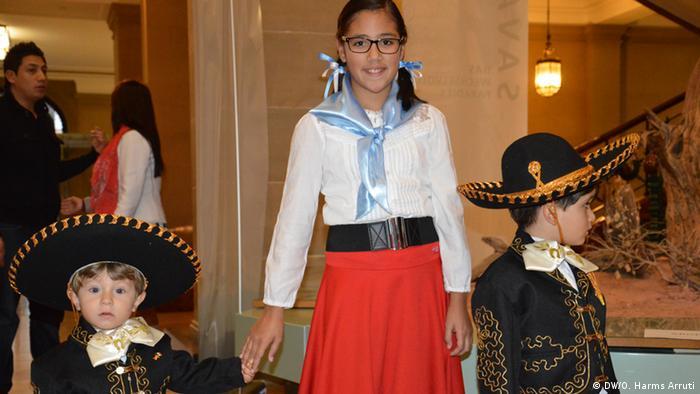 En el museo Alexander König se reunieron varios niños de todos los rincones del mundo a celebrar el Día Universal del Niño. Aquí una niña argentina lleva de la mano a dos pequeños que son mitad mexicanos, mitad alemanes. Los tres portan vestimenta tradicional argentina y mexicana.