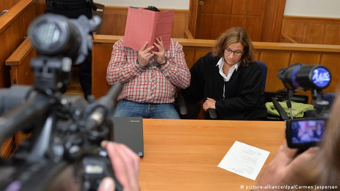 Nils H. sits in court, faced covered with a folder