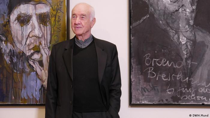 Armin Mueller-Stahl steht zwischen zwei Ölgemälden, abstrakte Portraits