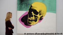 Eine Besucherin der Kunstsammlungen Chemnitz betrachtet am 21.11.2014 in Chemnitz (Sachsen) die Arbeit Skull (1976) von Andy Warhol. Bis zum 22. Februar 2015 zeigt das Museum 61 Bilder aus der bedeutenden Werkgruppe Death and Disaster. Foto: Hendrik Schmidt/dpa +++(c) dpa - Bildfunk+++