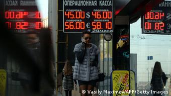 Pedestrians walk under a board listing foreign currency rates against the Russian ruble outside an exchange office in central Moscow Photo: VASILY MAXIMOV/AFP/Getty Images