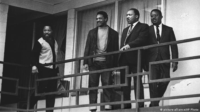 Martin Luther King stands on a balcony with Hosea Williams, Jesse Jackson and Ralph Abernathy