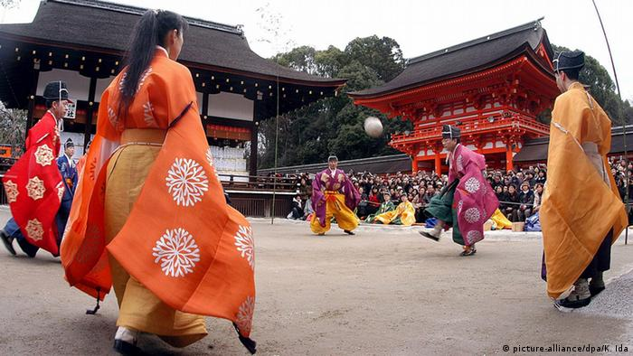Mehrere Personen in Kostümen spielen das Ballspiel Kemari. Foto: dpa